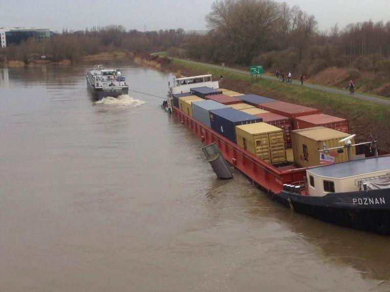 Een sleepboot probeert de Poznan tevergeefs vlot te trekken.