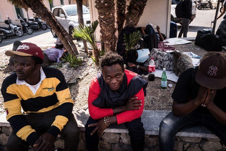 Migranten hangen voor het treinstation van Ventimiglia.  Beeld Nicola Zolin