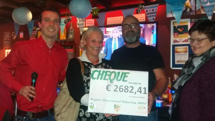 Jos Schapendonk die het Vughts duurrecord biljarten in 2017 op 41 uur, bracht, reikt de cheque met de opbrengst uit.