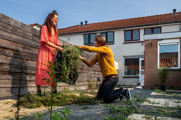 Roy Veer (33) en Jasmijn Hoekman (28) bezig met het opruimen van het onkruid in de tuin van hun nieuwe woning in Zuilen.