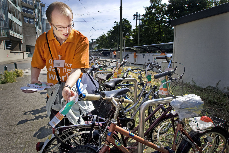 Een wajonger hangt flyers op aan fietsen om actie te voeren voor banen voor jonggehandicapten.