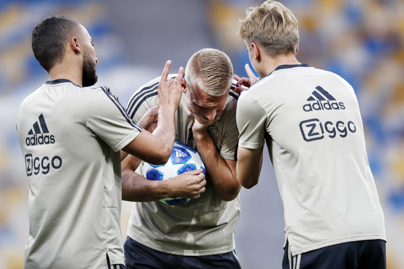 Zakaria Labyad, Mitchell Bakker en Dennis Johnsen dollen tijdens de training van Ajax in het NSK Olimpiejsky-stadion in Kiev.