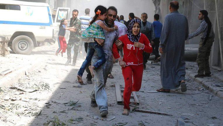 Burgers rennen voor dekking na een luchtaanval in Aleppo
