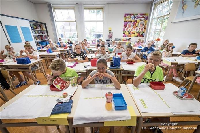 De kinderen van groep 8A leggen netjes de theedoeken over hun tafelbladen en beginnen te eten, terwijl ze het jeugdjournaal kijken. Jorn Pigge (vooraan links) denkt dat sommige kinderen niet durven toegeven dat ze de anderhalf uur pauze thuis missen.