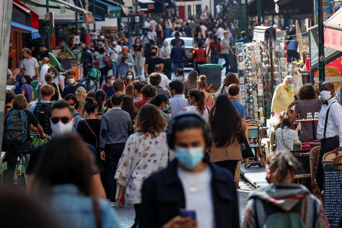 Voorbijgangers dragen maskers in een drukke straat in Parijs.