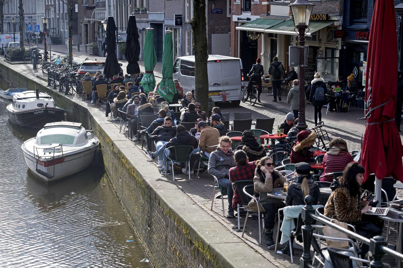 Mensen genieten op een terrasje aan een gracht in Amsterdam.