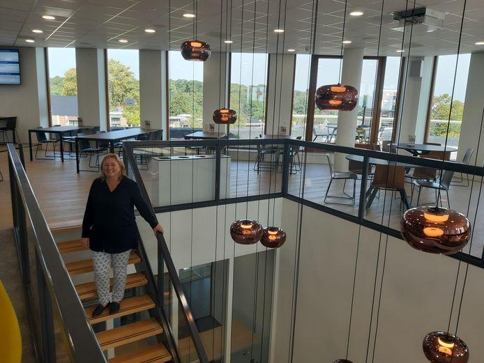 Caroline Elias van Hoogwegt daalt de trap af vanuit het nieuwe bedrijfsrestaurant met dakterras en uitzicht op het station, het centrum en het Sonsbeekpark.