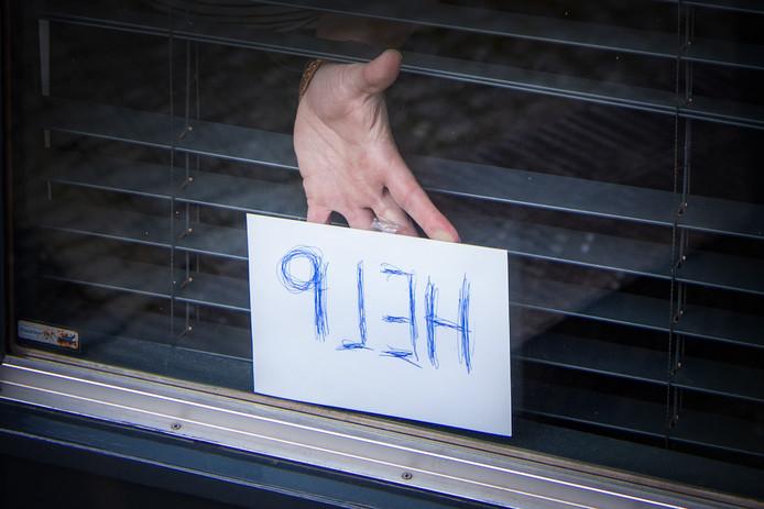 Het briefje waarmee het echtpaar de aandacht van een passant wist te trekken, nadat ze door de overvallers in een kamer waren opgesloten.