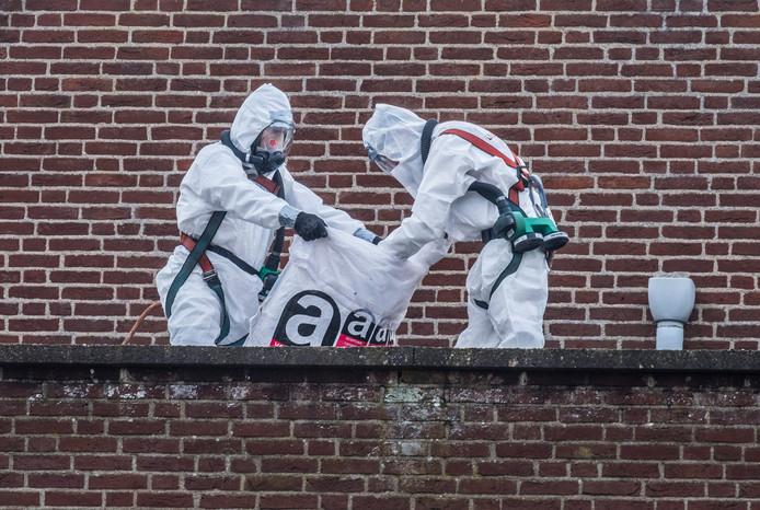 Twee werklieden verwijderen asbest, gehuld in beschermende pakken