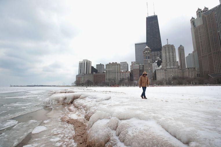 Het lijken schuimende golven, maar het is zand bedekt met sneeuw en ijs. Een wandelaar waagt zich langs Lake Michigan, Illinois.