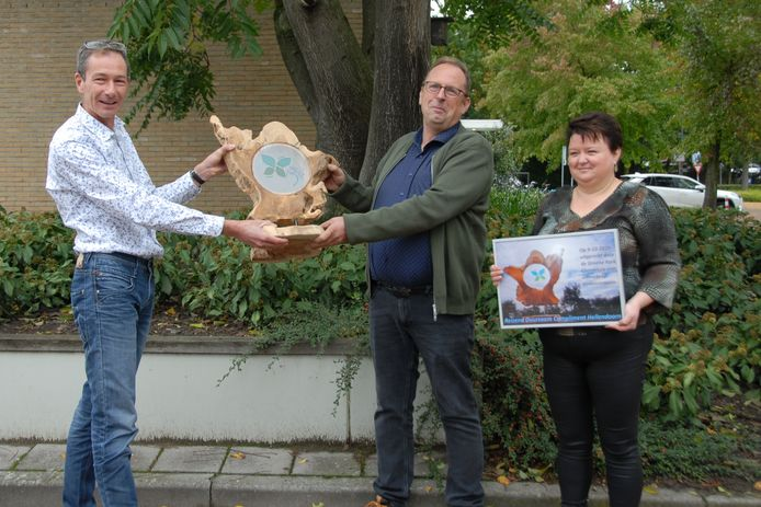 Dick de Vente (links) overhandigt het Reizend Duurzaam Compliment aan Wielent Zonnebeld en zijn vrouw.