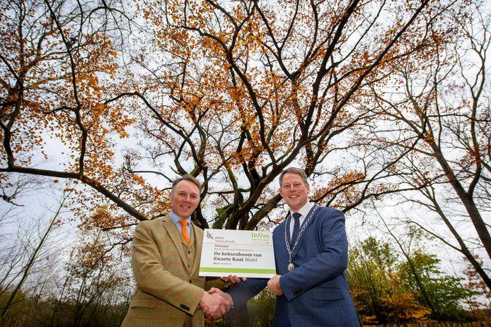 Bladel heeft met de Heksenboom de mooiste boom van Nederland in haar gemeente. Willem Schimmelpenninck van der Oije, directeur van SBNL Natuurfonds (l) reikte gisteren de prijs uit aan burgemeester Remco Bosma.