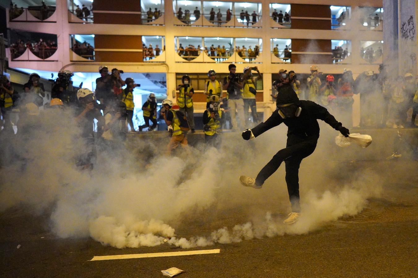 Een demonstrant schopt tegen traangas dat door de politie is gegooid.