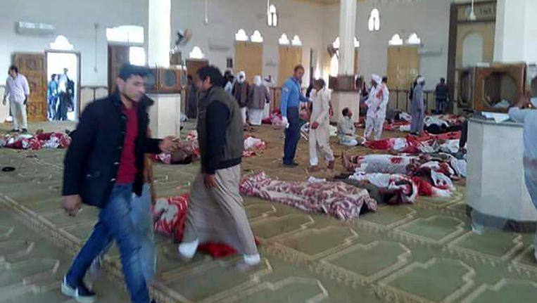 Egyptenaren lopen langs de lichamen in de gebedsruimte van de moskee. Beeld afp