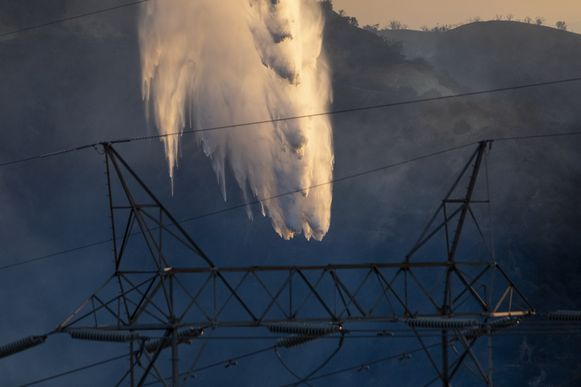NEWHALL, CA - OCTOBER 11: A firefighting helicopter drops water on the Saddleridge Fire near high power lines on October 11, 2019 near Newhall, California. The fire has spread to 7500 acres and burned at least two dozen homes   David McNew/Getty Images/AFP == FOR NEWSPAPERS, INTERNET, TELCOS & TELEVISION USE ONLY ==