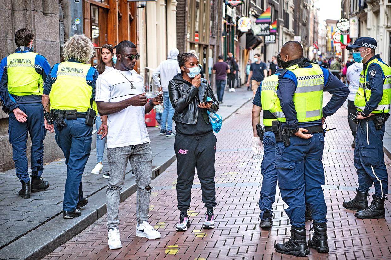 Op De Wallen worden mensen aangesproken die zich niet aan de mondkapjesverplichting houden, die in de zomer op sommige drukke plekke in Amsterdam van kracht was.   Beeld  Guus Dubbelman / de Volkskrant