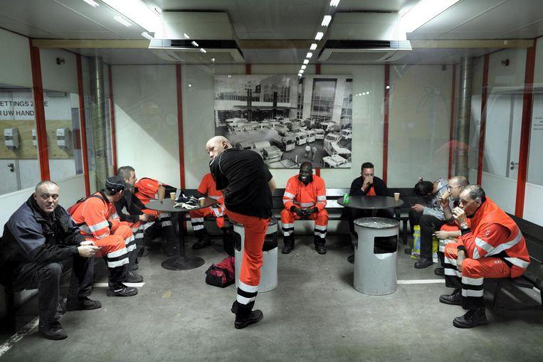 Amsterdamse vuilnismannen en straatvegers doen een pafje in de rookruimte. Beeld null