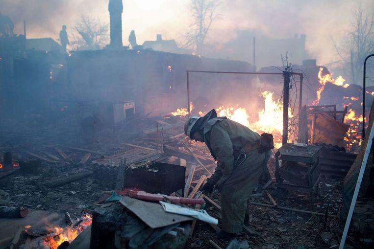 Een brandweerman staat tussen de overblijfselen van enkele huizen nabij de stad Donetsk. Beeld afp