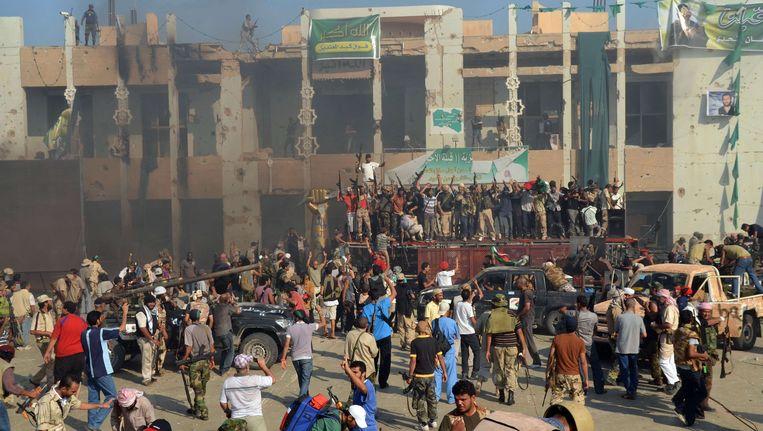 Rebellen vieren feest op het ingenomen hoodfkwartier van Kaddafi. Beeld afp