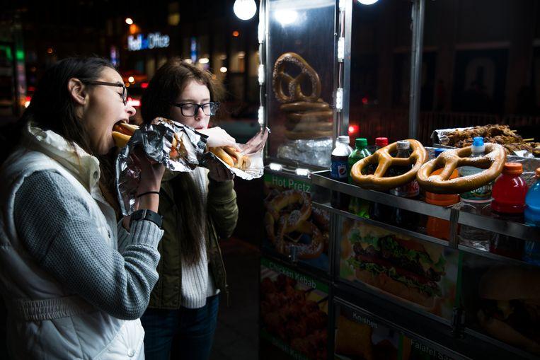 Twee tieners storten zich op fastfood.