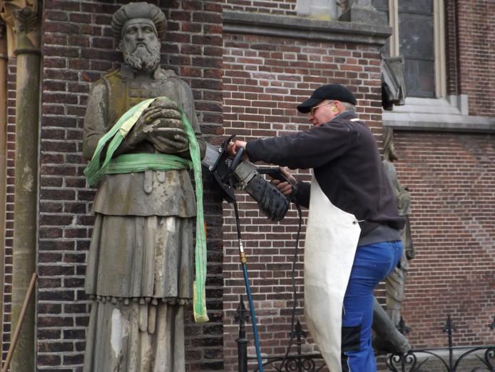 Beeldhouwer Koen van Velzen zaagt de beelden van de muur van de Lambertuskerk in Veghel.