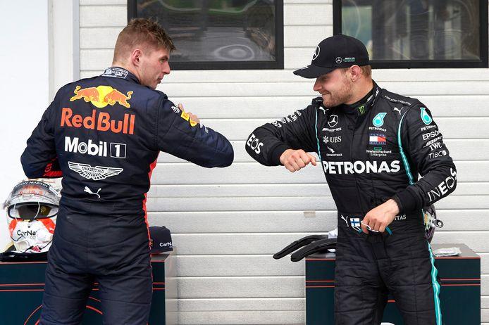 Max Verstappen en Valterri Botas geven elkaar een elleboog.