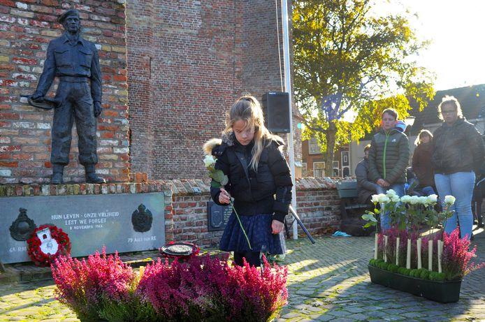Deborah (10) uit groep 6 van de Eben Haëzerschool legt een bloem tijdens de herdenking.