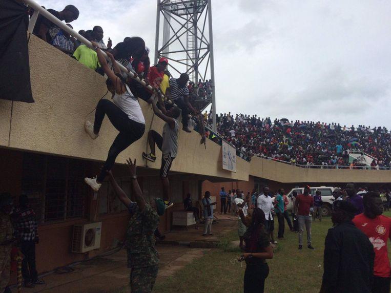 Gambiaanse fans proberen aan de overvolle tribunes te ontkomen.