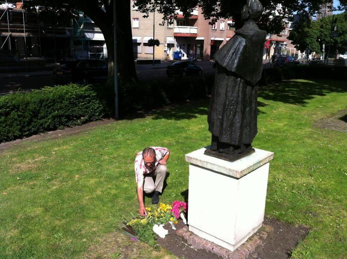 Johan Wagemakers schikt de bloemen die bij het standbeeld van Titus Brandsma zijn gelegd.