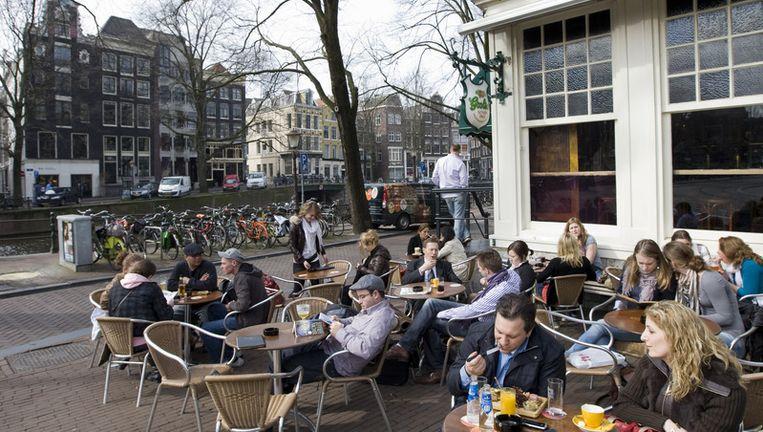 In Amsterdam is het niet toegestaan om staand te drinken op een terras. Foto ANP Beeld