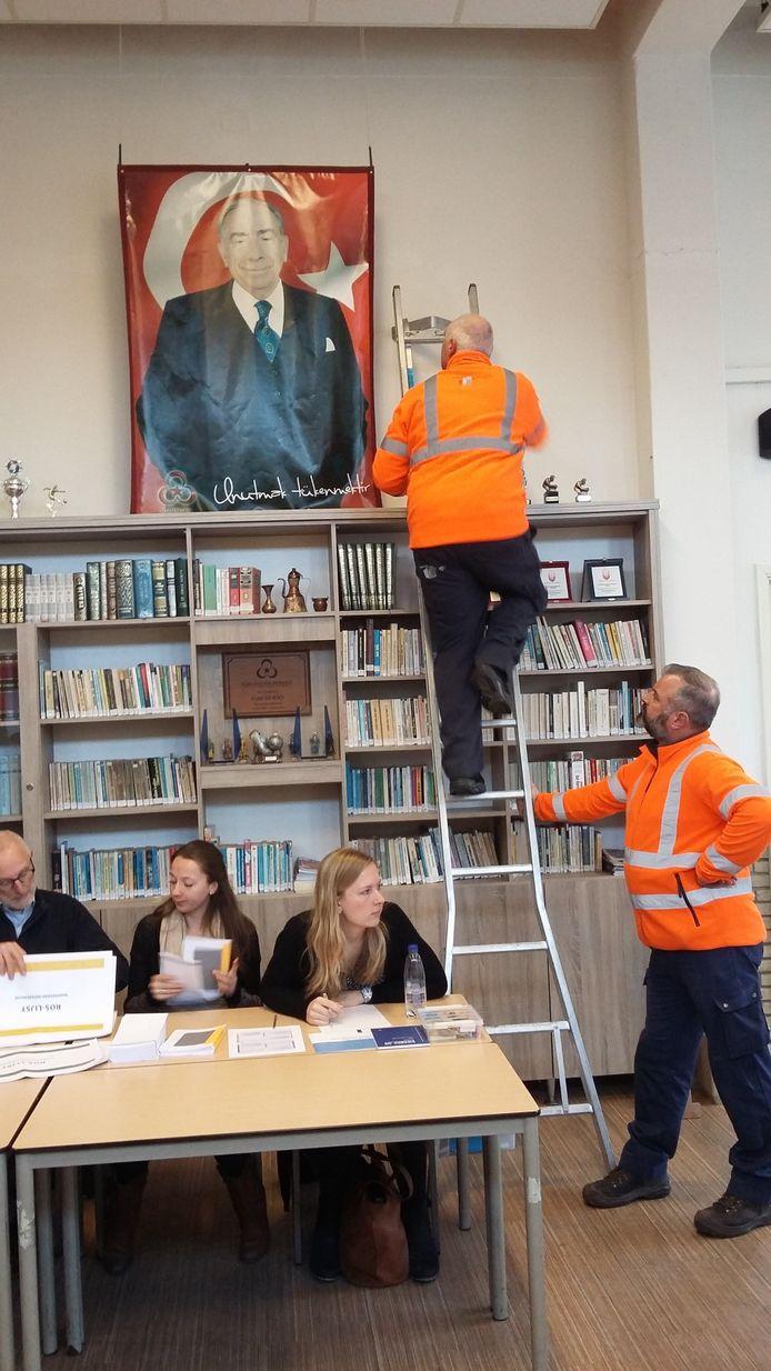 Medewerkers van de gemeente verwijderen Turkse uitingen uit het stemlokaal in Nijmegen.