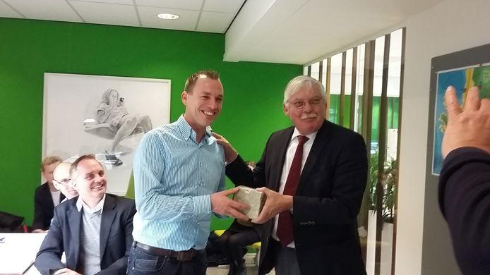 Burgemeester Van der Knaap schenkt de steen aan de initiatiefnemers.