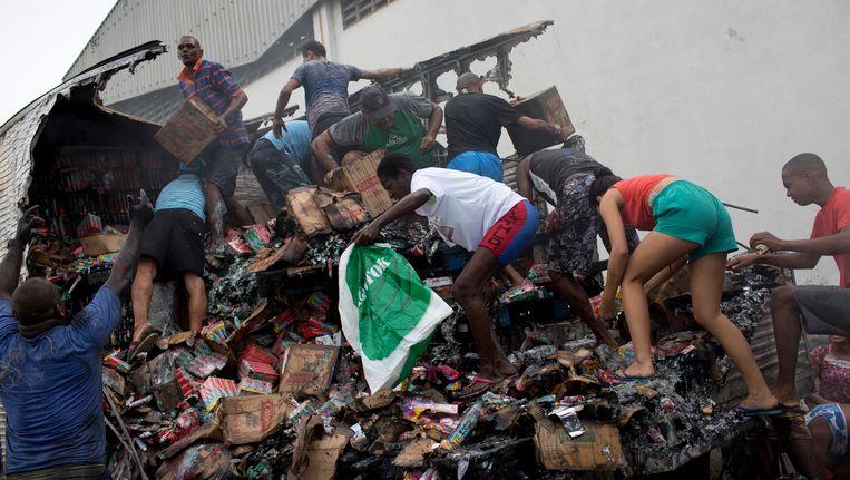 Mensen klimmen op de lading van de uitgebrande vrachtwagen om te redden water nog te redden valt.