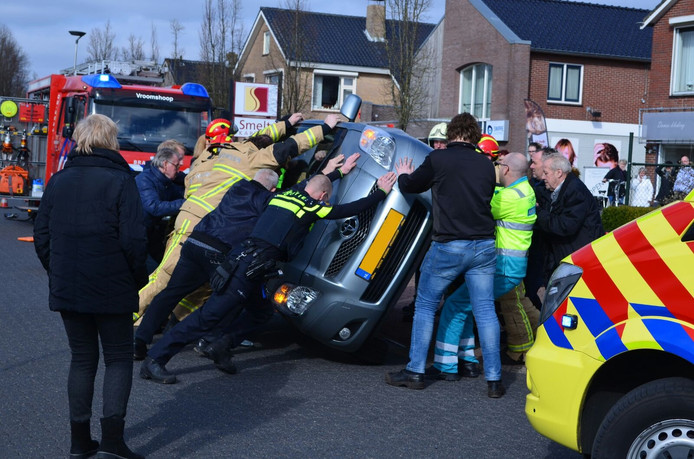 Politie, brandweer en omstanders duwden de auto weer op zijn wielen.