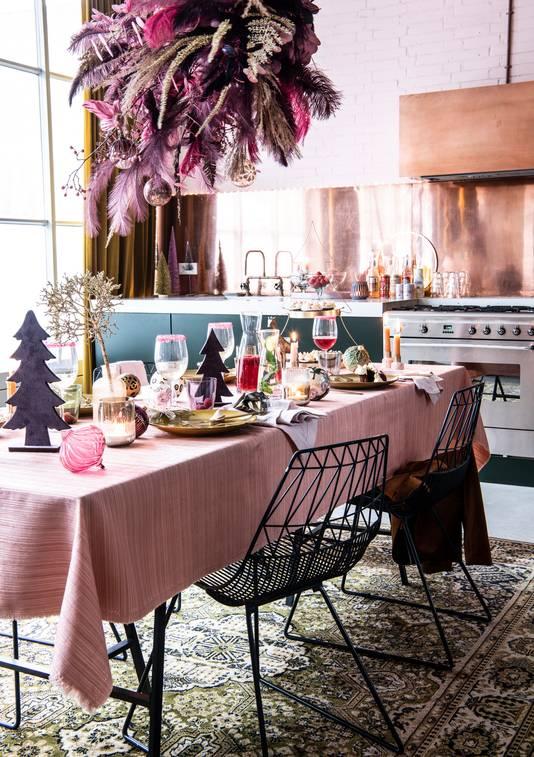 Kersttafel met lichte kleuren en pluimen.