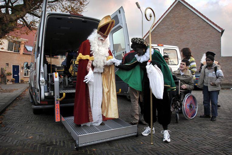 Wie zoet is krijgt lekkers, wie stout is de roe. Sint en Piet op bezoek in Haarlem. Beeld Joost van den Broek