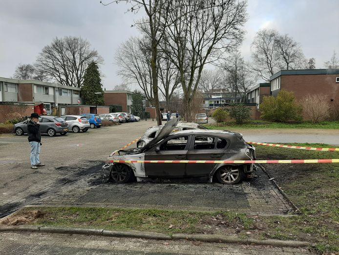 Een buurtbewoner staat naar de twee verwoeste auto's aan de Apeldoornse Imkersdreef te kijken.