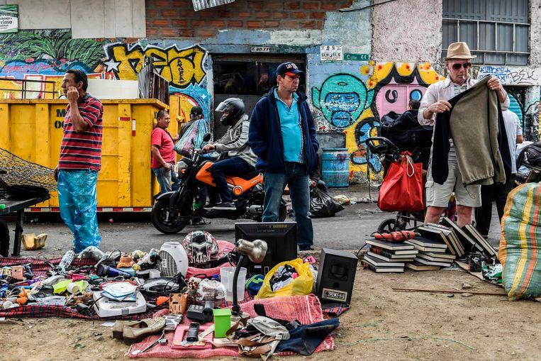 Mensen kijken naar tweedehands producten op straat. Beeld AFP