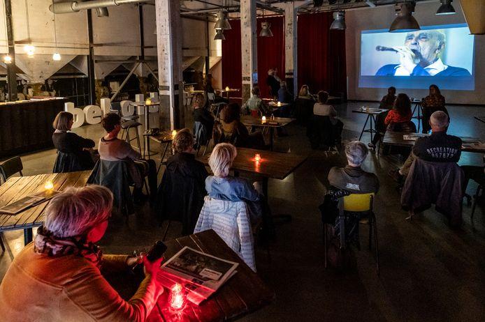 In een ongedwongen setting kijken de bezoekers op de Noordkade naar de documentaire 'Here I Am'.