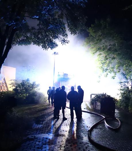Grote hoop snoeiafval brandt vlakbij houten schuur bij Wilgje Buitensport in Buren