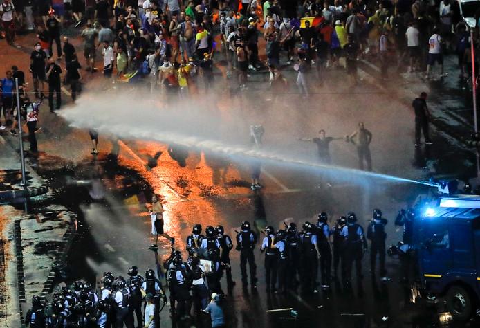 De politie zet traangas en waterkanonnen in.