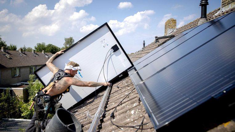 Op een woonhuis worden zonnepanelen geplaatst. Beeld anp
