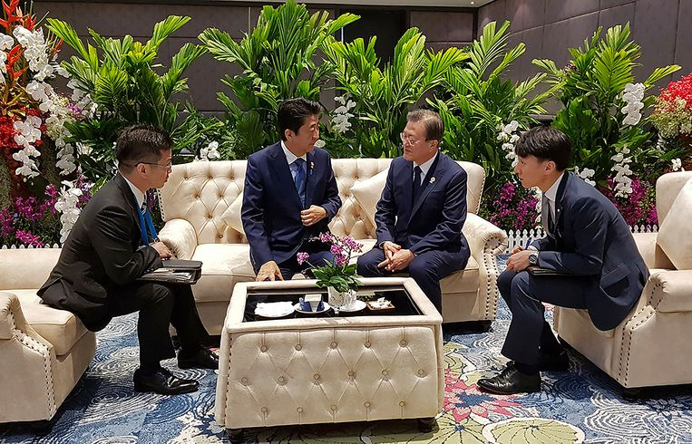 De Zuid-Koreaanse president Moon Jae-in (midden-rechts) spreekt met de Japanse premier Shinzo Abe (midden-links) voorafgaand aan de ASEAN+3-top in Thailand. Beeld AP