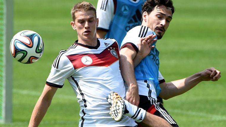 Lars Bender (L) op de training in duel met Mats Hummels.