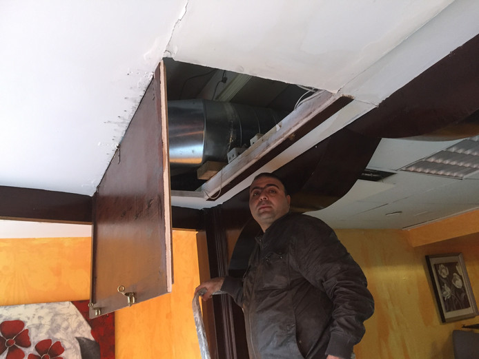 Ibrahim Alzoubi kijkt naar de schade in de luchtschacht van zijn restaurant Bloem van Damascus in Breda.