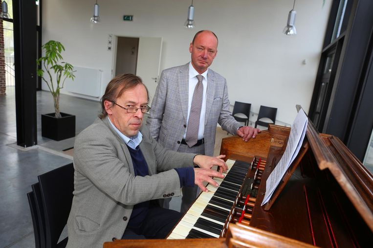 Organist Walter Callaert en schepen David De Valck bij het historische harmonium.