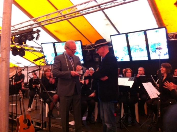 Burgemeester Jan Boelhouwer overhandigt de onderscheiding. Foto Ron van Kuijk