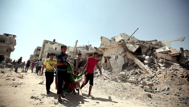 Palestijnen dragen een lichaam in een deken in het dorp Khan Yunis op de Gazastrook, om hen heen kapotgeschoten huizen. Beeld getty