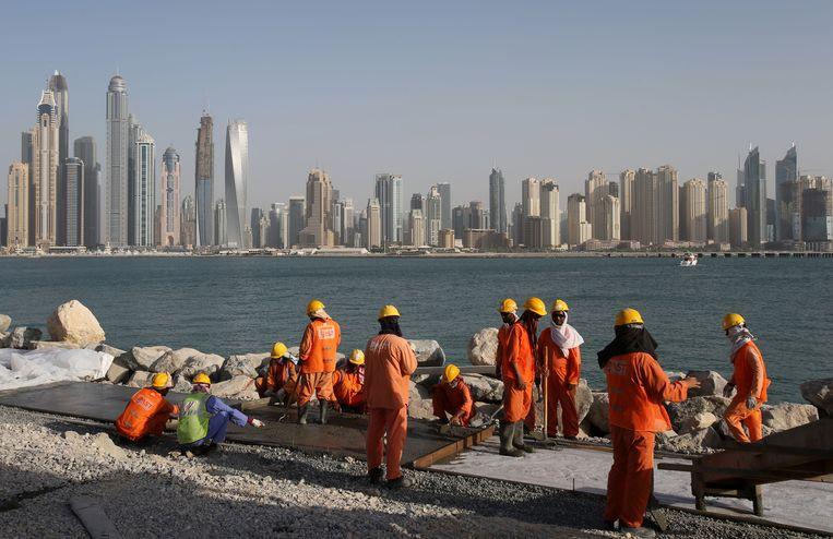 Arbeiders aan het werk in Dubai, de Verenigde Arabische Emiraten. Migranten zijn kwetsbaar voor arbeidsuitbuiting. Beeld AP