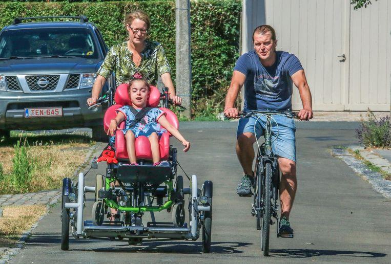 Ella in haar nieuwe elektrische rolstoelfiets, samen met mama Kaat D'haene en papa Dominique Dubus
